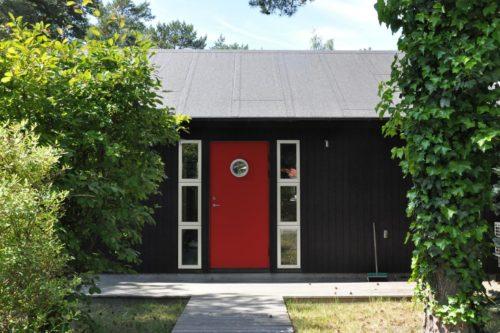 svart trähus med röd dörr